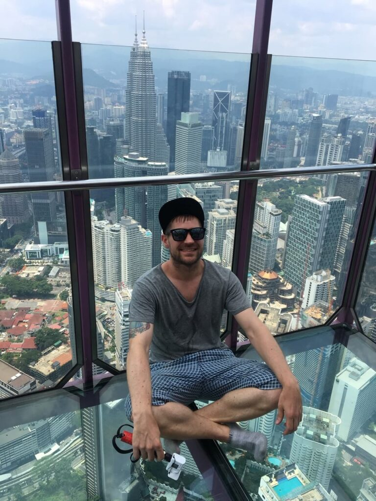 Eivind from Norway Couchsurfing posing with a casual yoga posa above a transparent flooring in a tower in Malaysia