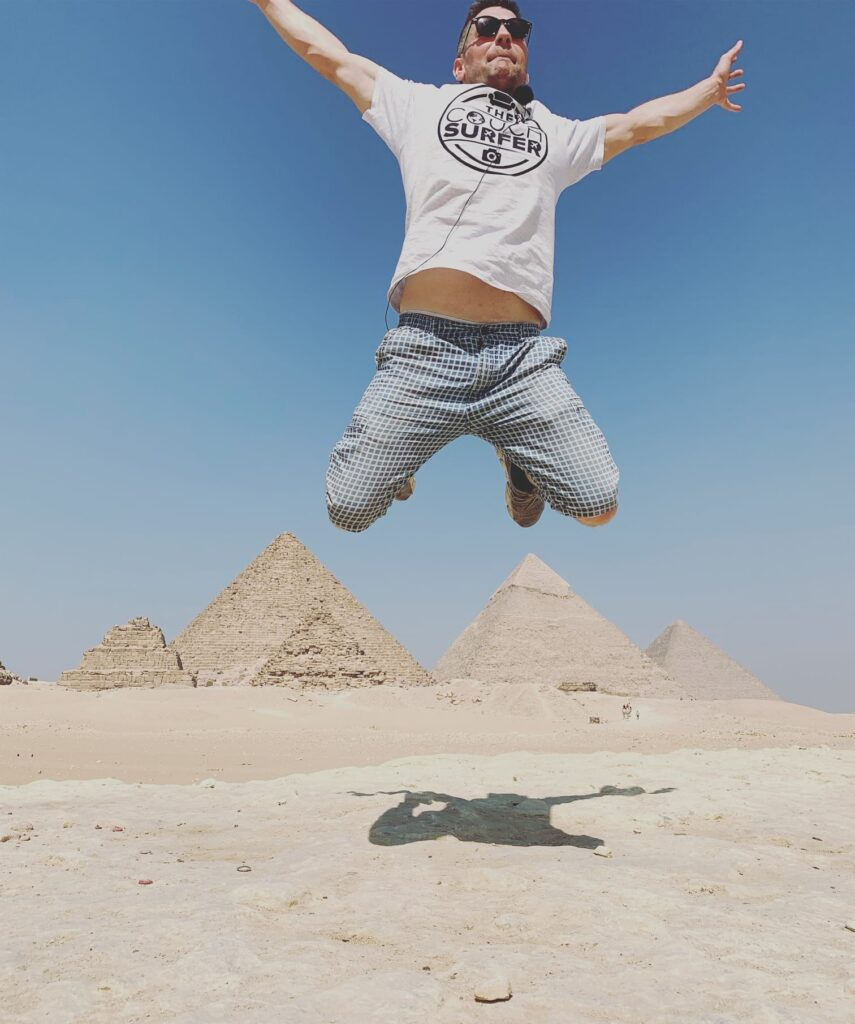 Eivind jumping with the Pyramids behind him. Egypt Couchsurfing.