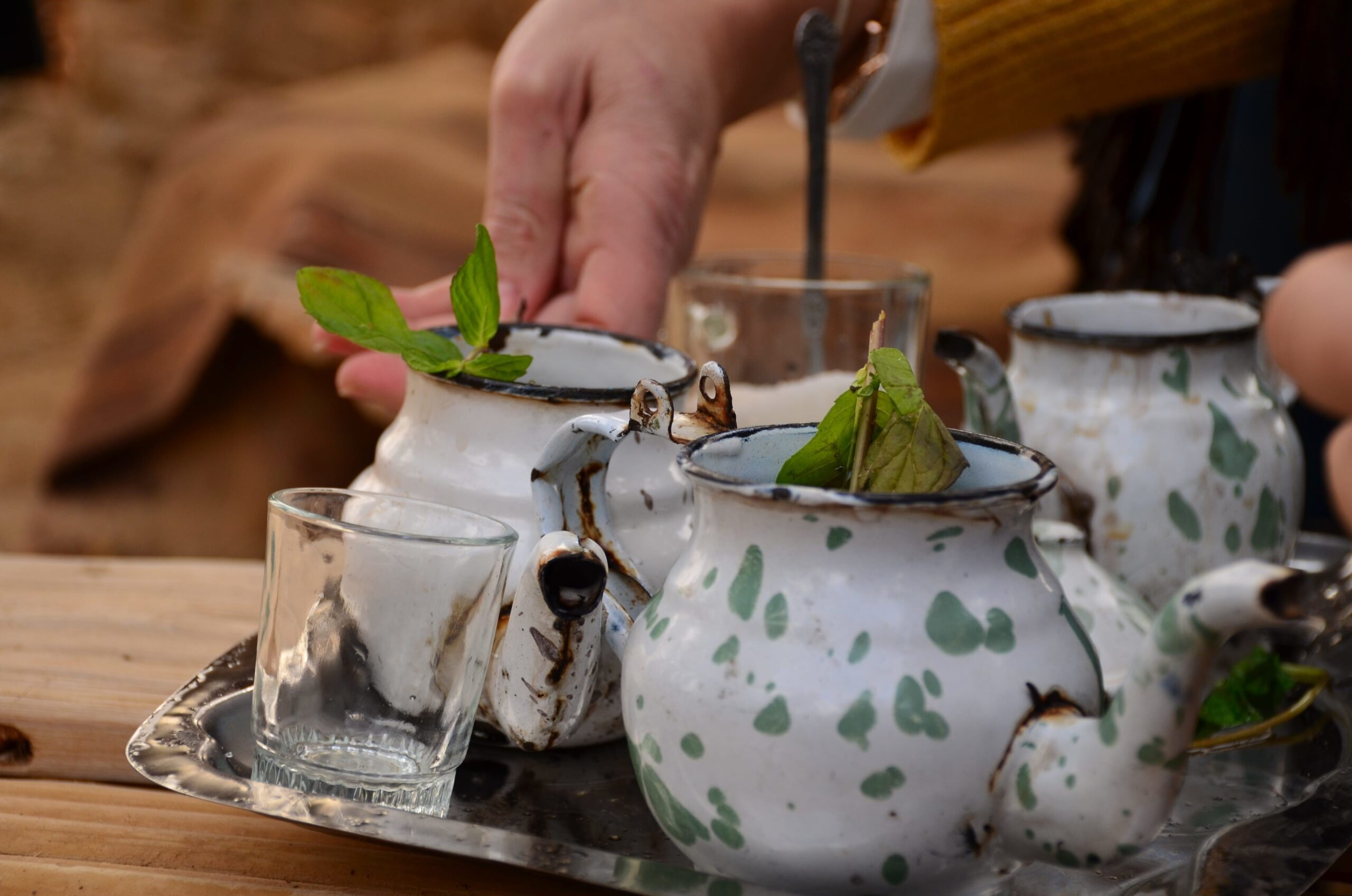 Tea being served with mint leaves in the pot