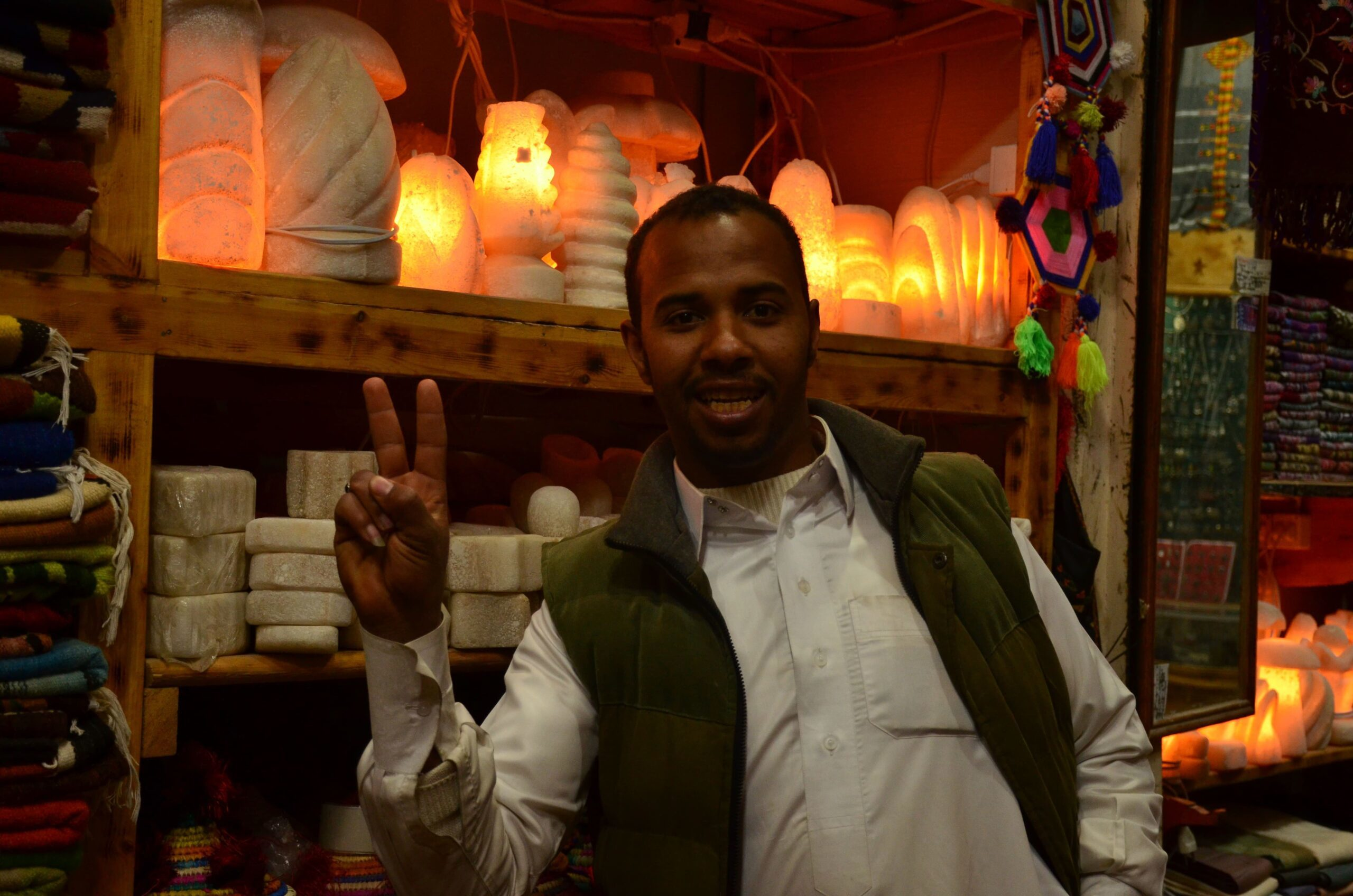 Man posing with peace sign at a store in Siwa