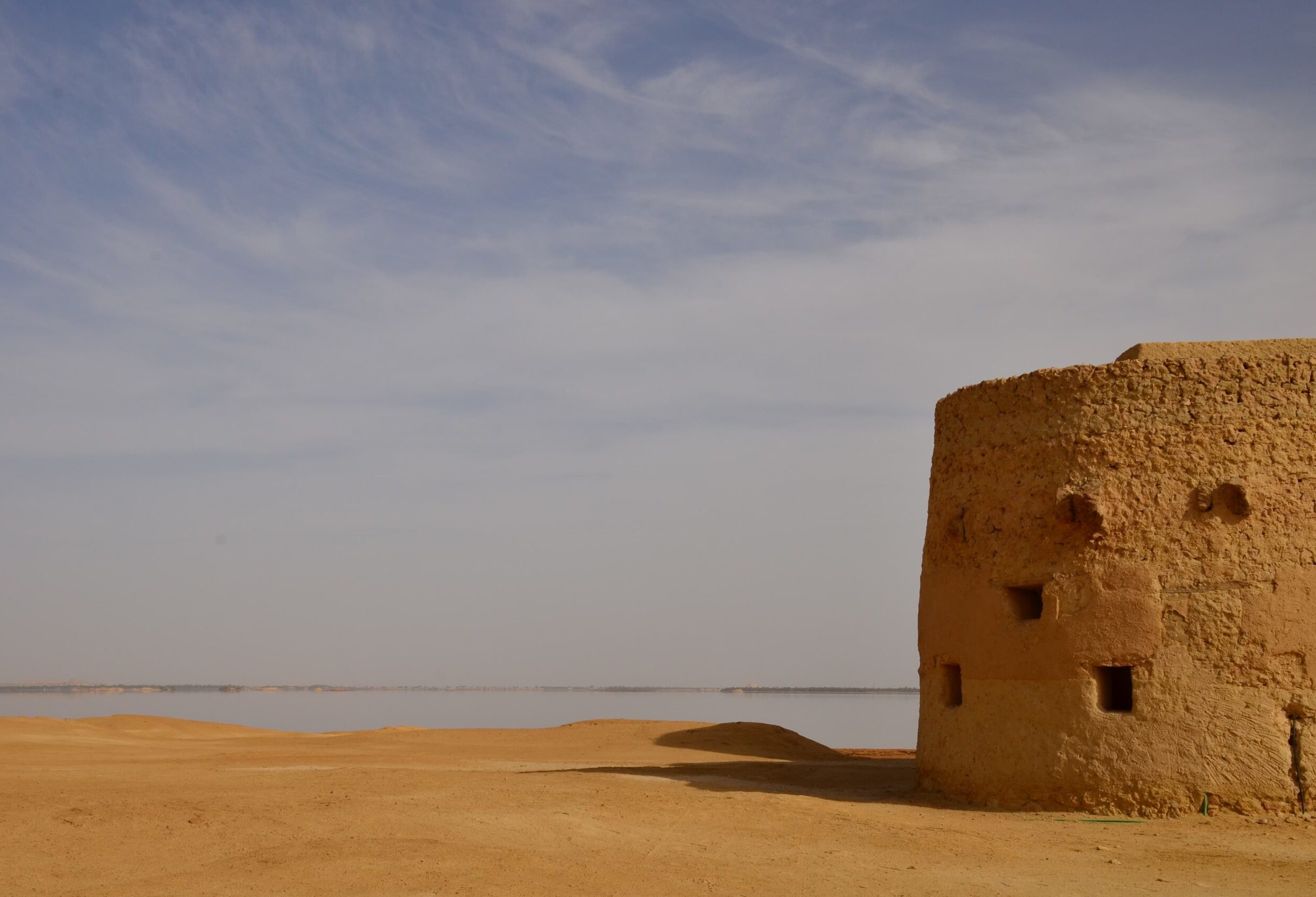 Shali Fortress by a sunny day casting its shadown on the sand