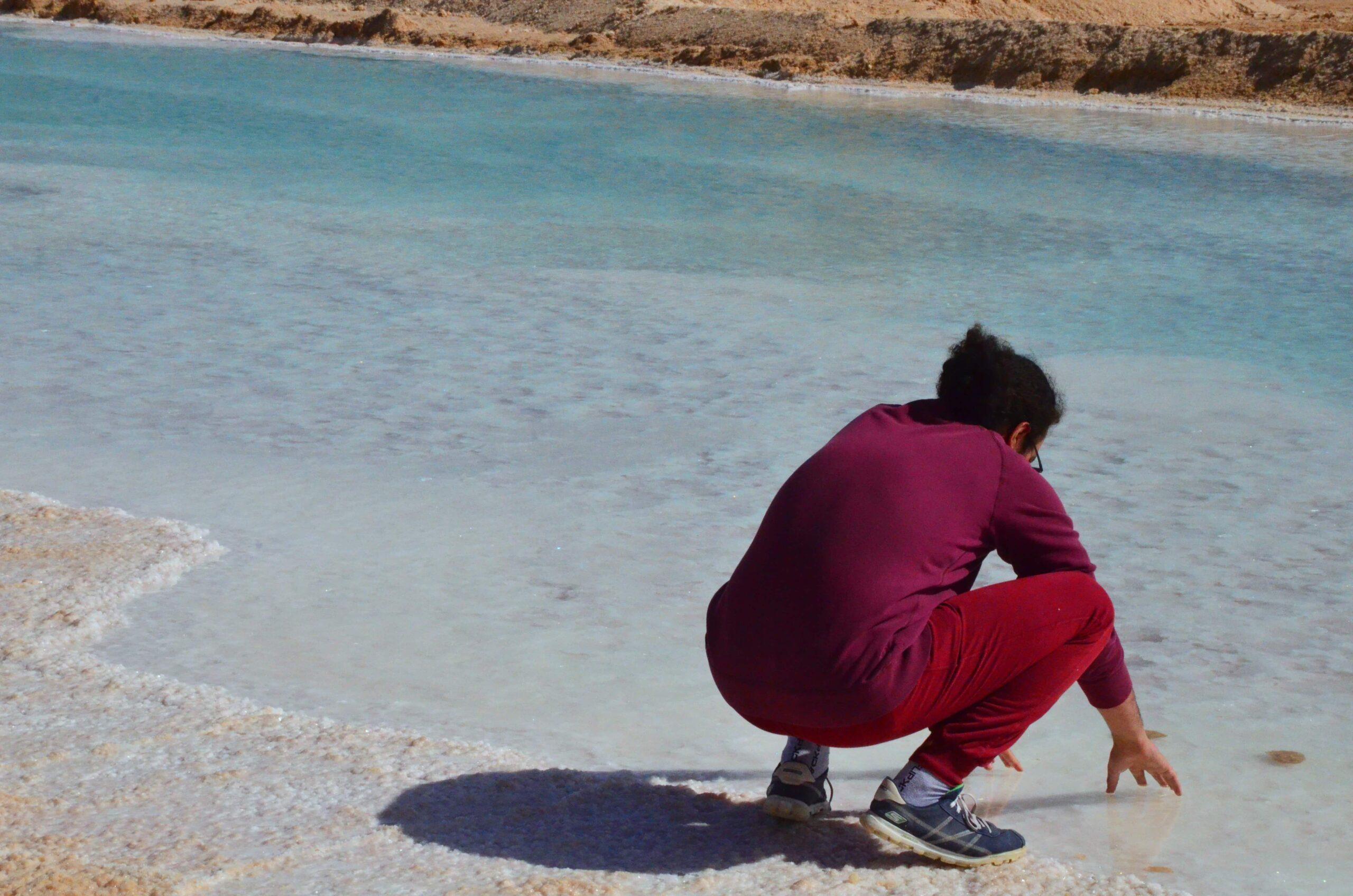 man half sitting by lake in Siwa