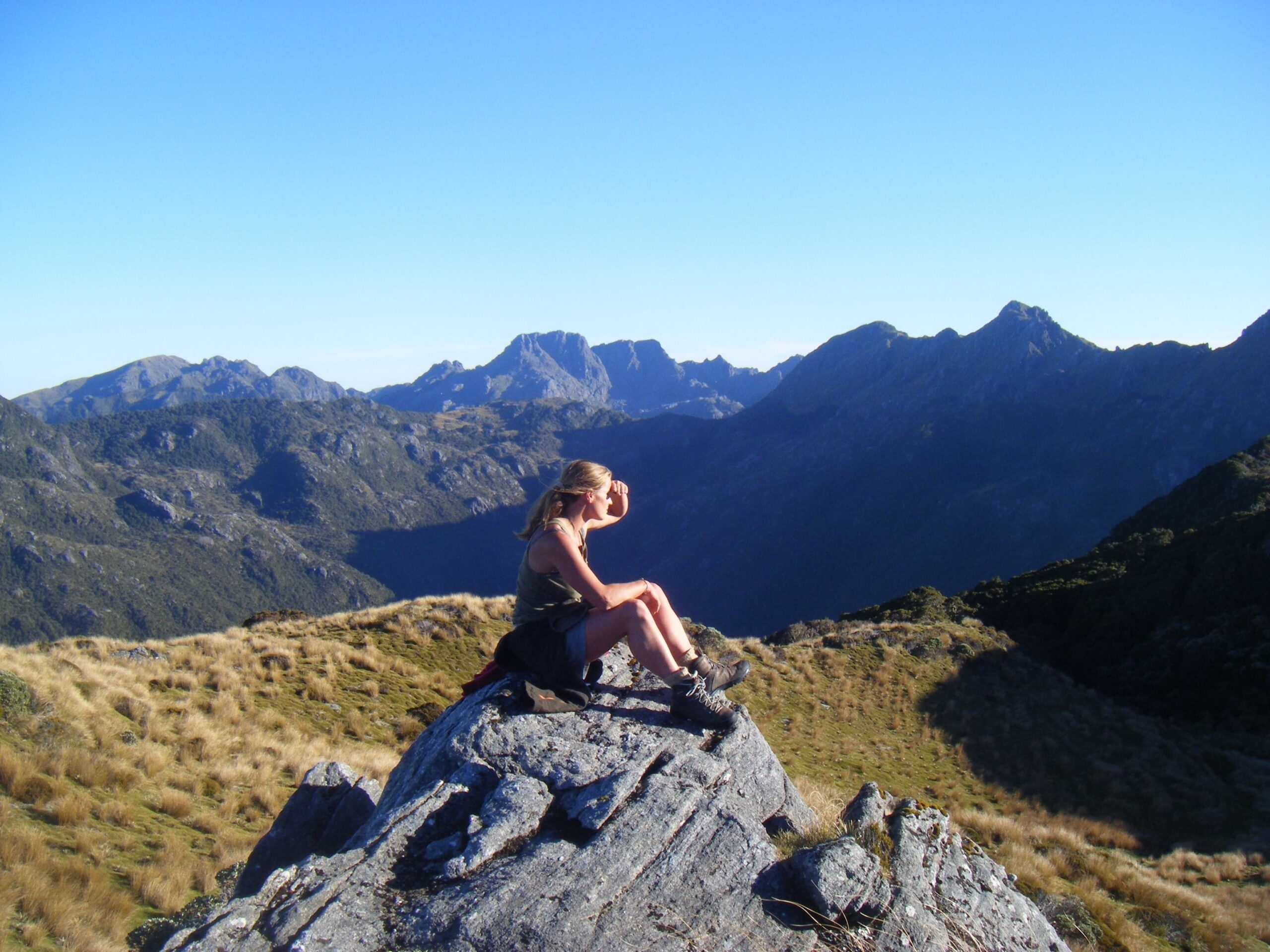 Miriam Lancewood sitting on a rock overlooking mountains