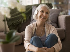 A senior woman listens to music through headphones as part of Music and Memory.