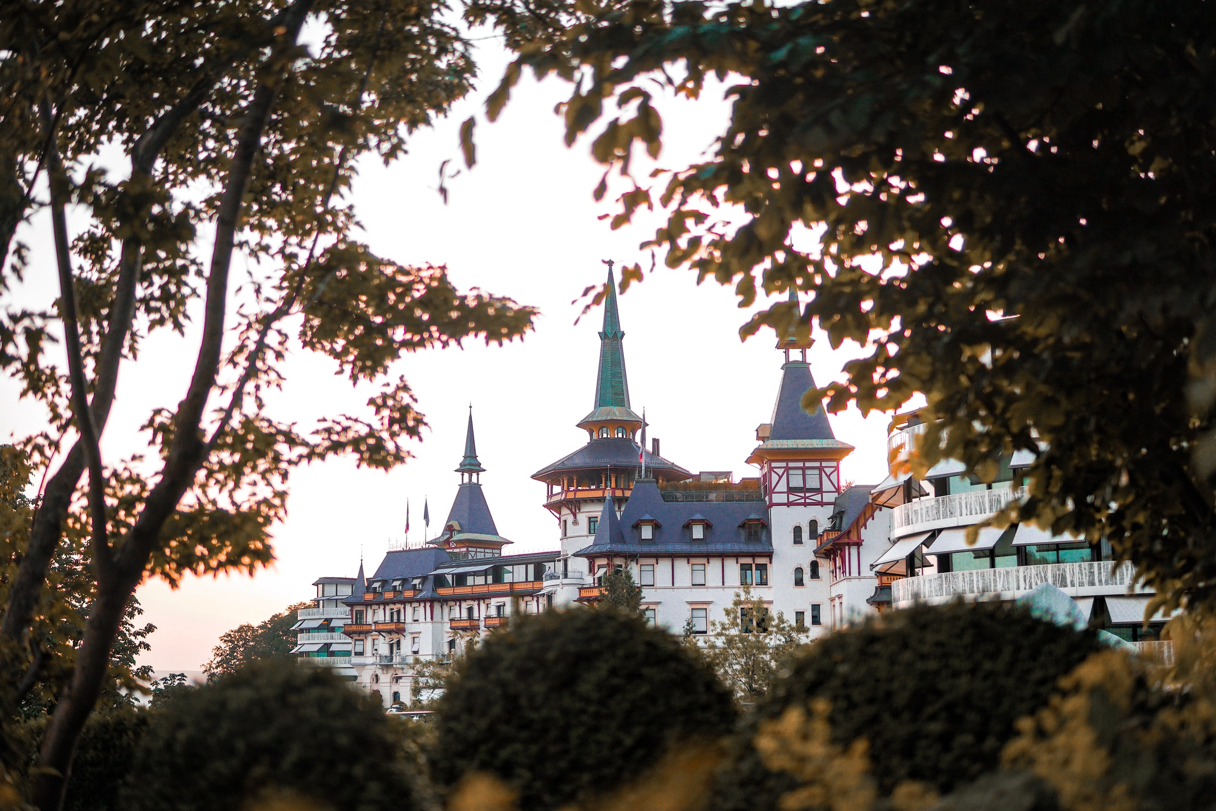 Towers of the exclusive Dolder Grand Spa seen through trees