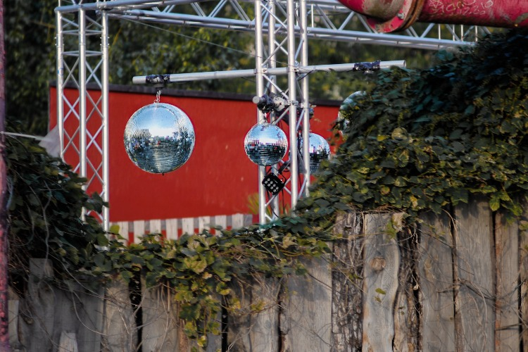 Disco balls hanging in front of a club's red wall in Berlin, Germany