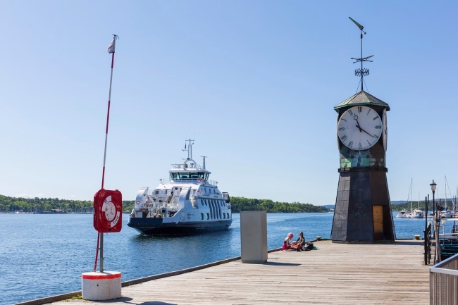 Two people sit in the sun by the clock at Aker Brygge while the ferry passes by