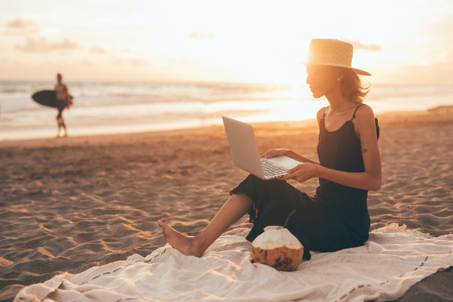 Woman in black dress and hat on blanket at the beach with laptop