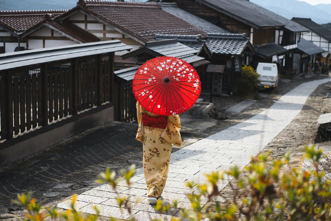 Woman in Japanese attire walking through a Japanese neighborhood with wagasa umbrella