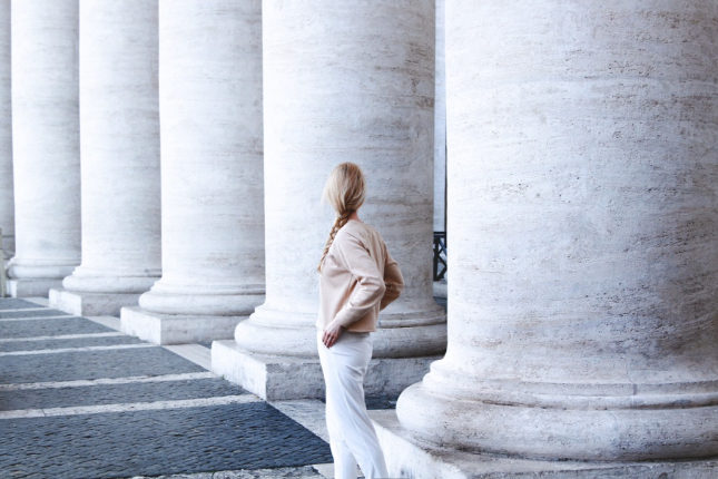 Solitary blonde woman with braid facing away from camera next to a long row of columns