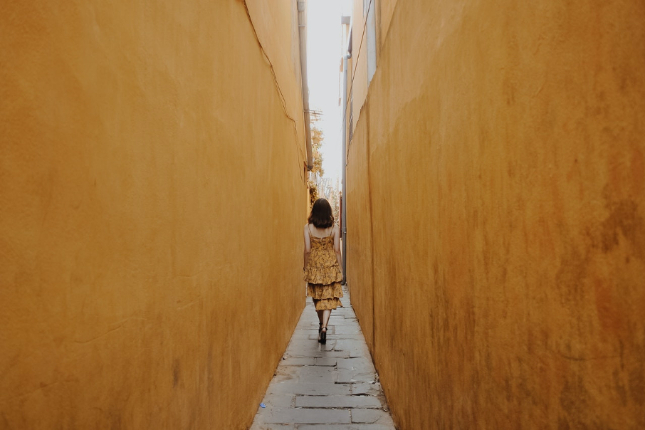 Woman in frilly yellow dress walking down narrow alley of yellow walls