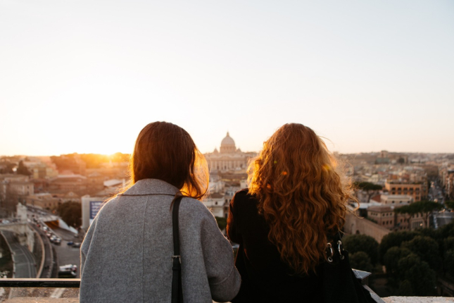 Two women looking over a rooftop view of a city with the sun setting