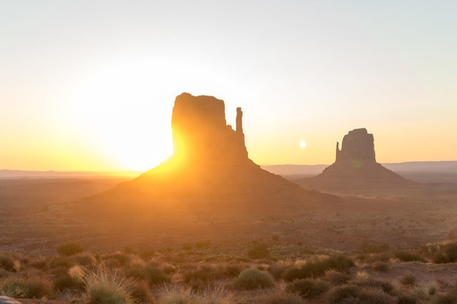 Sun setting behind mesa in Monument Valley, US