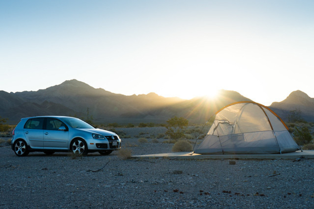 Car and tent bathed in light in front of hills in Death Valley