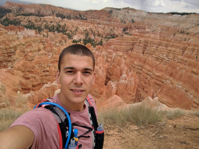 Man in pink shirt with hiking equipment in front of Brice Canyon
