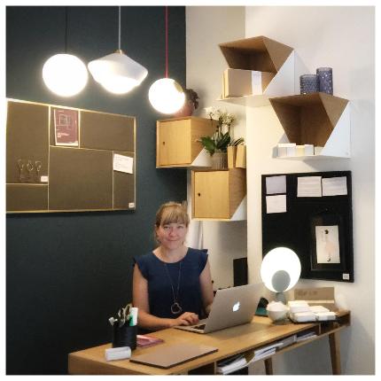 Julie Marie Kjersem sitting behind her desk in front of a blue wall