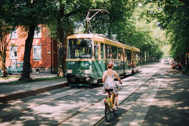 Tram passes woman on bike along tree-lined Helsinki street