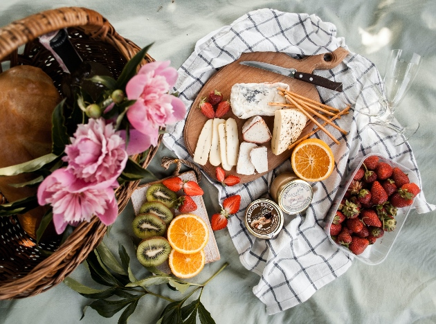 Picnic blanket in Paris park spread with cheese and wine