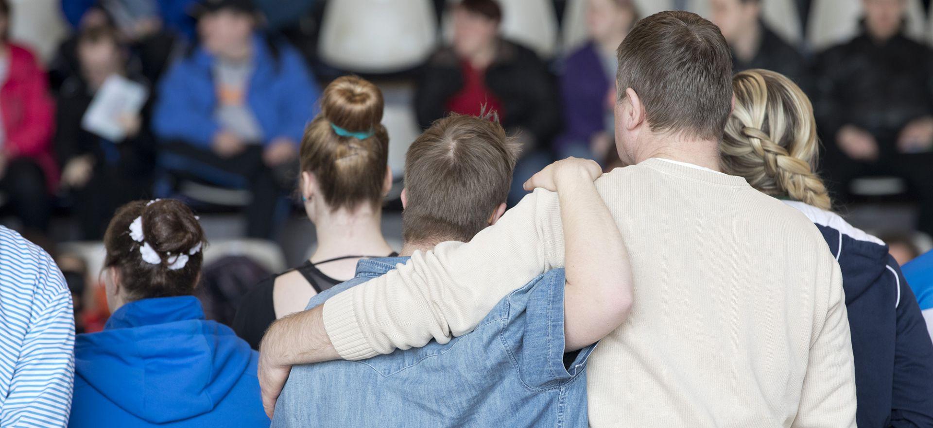 Mies ja poika kädet toistensa harteilla.