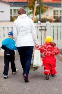 Kuvassa vanhempi kävelee taluttaen kahta lasta