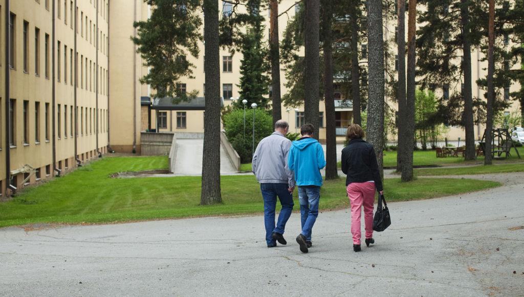 Kuvituskuvassa perhe kävelee asumisyksikön pihalla. Kuva: Laura Vesa