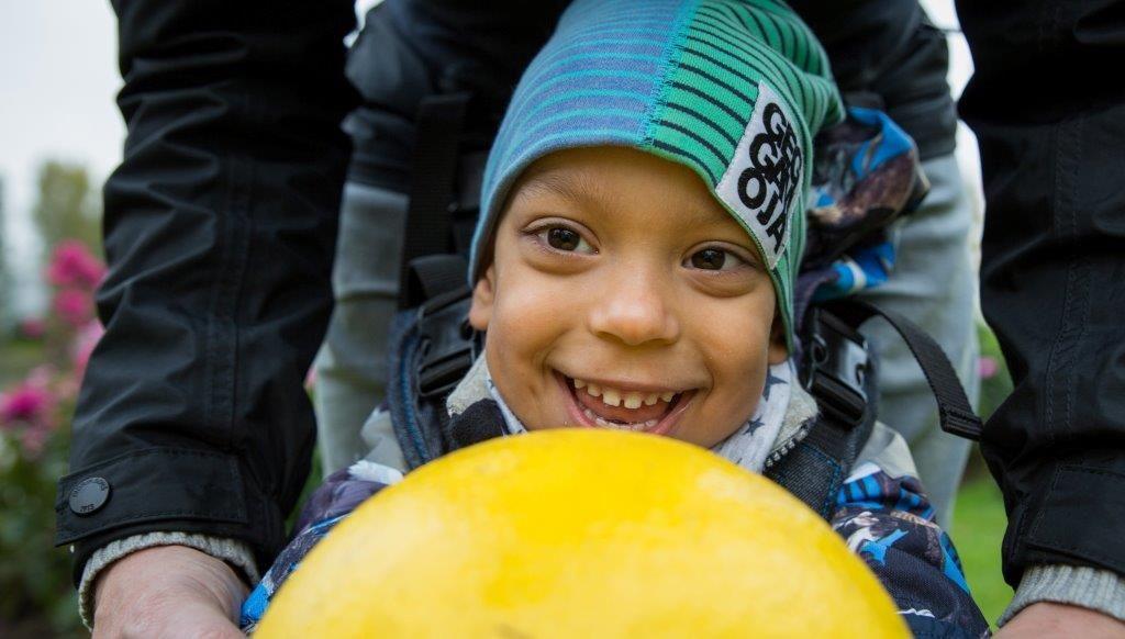 Jacob-poika hymyilee pelatessaan pallolla.