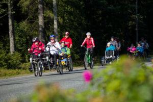 Joukko ihmisiä pyöräilee avustettuna erityispolkupyörillä. Kuvassa rinnakkainpoljettava- ja yhdistelmäpolkupyörä.
