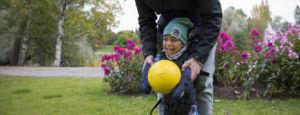 Pikkupoika pelaa palloa pystyasennon tuen avulla.