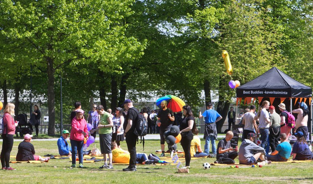 Ihmisiä kesällä aurinkoisessa puistossa.