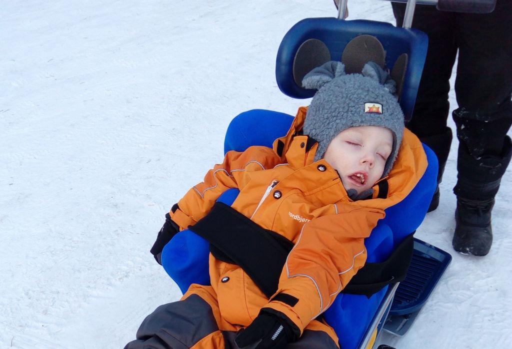 Wihtori istuu Snow Comfort -kelkassa. Hänen istuma-asentonsa on tuettu Stabilo-asentotyynyllä