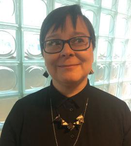 Oululainen äiti Leena Jumisko ottaa kantaa myös asusteillaan: kierrätyskorut on tehty Ei myytävänä! -kampanjan julisteista. Kuva Merja Määttänen.