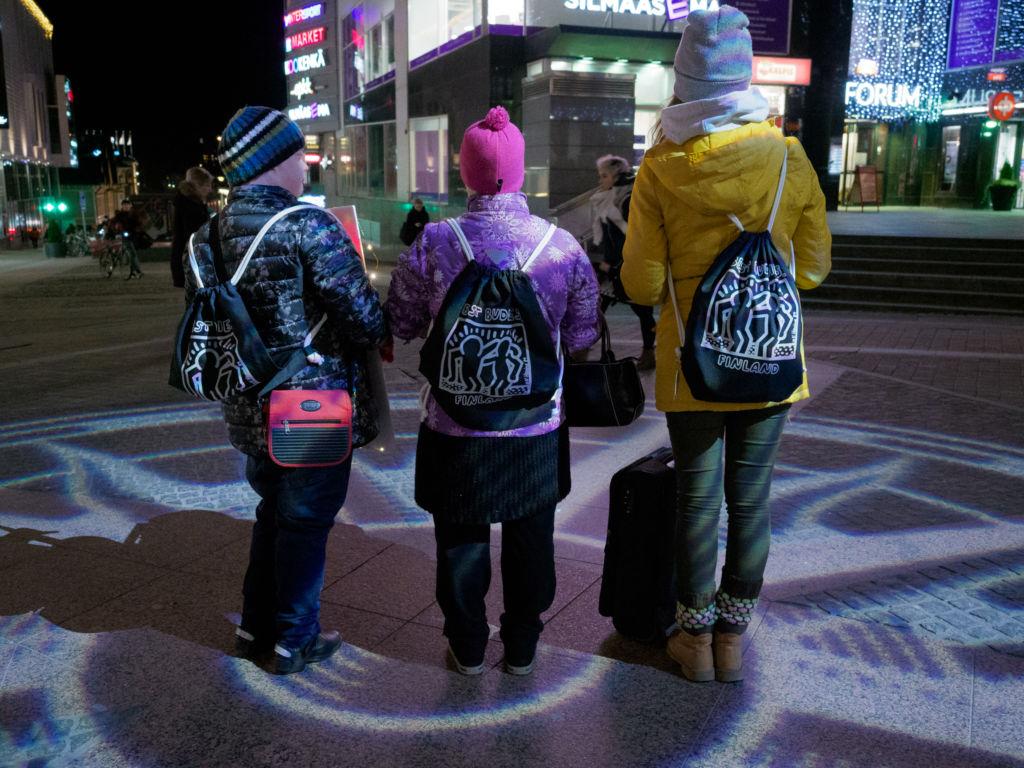 Vapaaehtoiset jakavat joulukortteja ohikulkijoille jouluisella kadulla, yväskylän keskustassa.