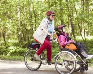 Tyttö ja nainen pyöräilevät yhdistelmäpyörällä. Tyttö istuu edessä olevassa istuimessa ja nainen polkee ja ohjaa pyörää.