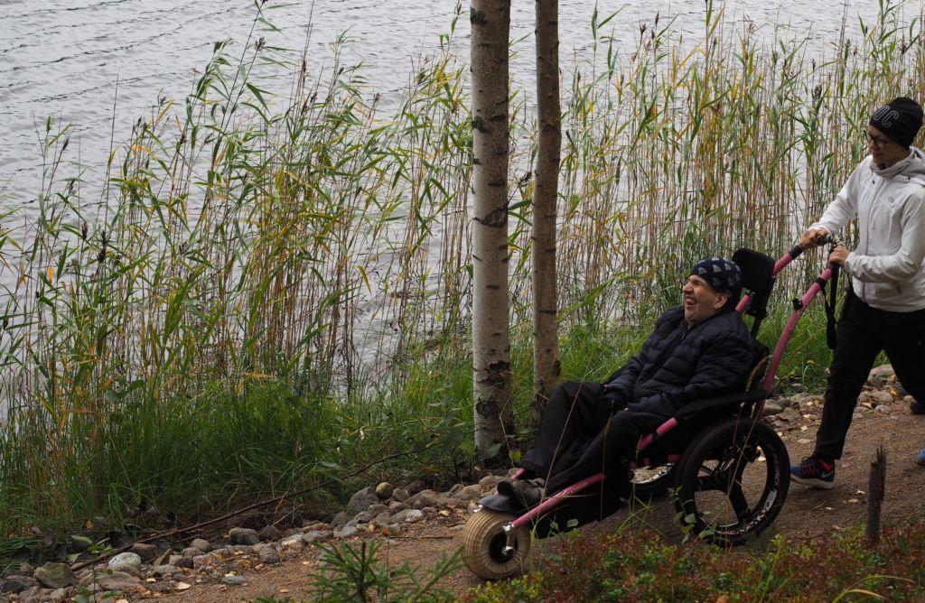 Mies istuu Hippocampe-maastopyörätuolissa, jota nainen työntää. He retkeilevät luontopolkua pitkin. Maisema on syksyinen ja taustalla näkyy järvi.