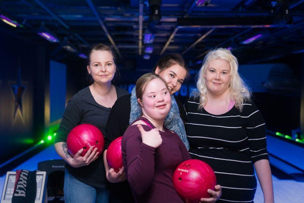 Joukko Jyväskyläläisiä naisia hymyilee kameralle keilapallot käsissään kaveritoiminnan Kohtaa mut -tapahtumassa.