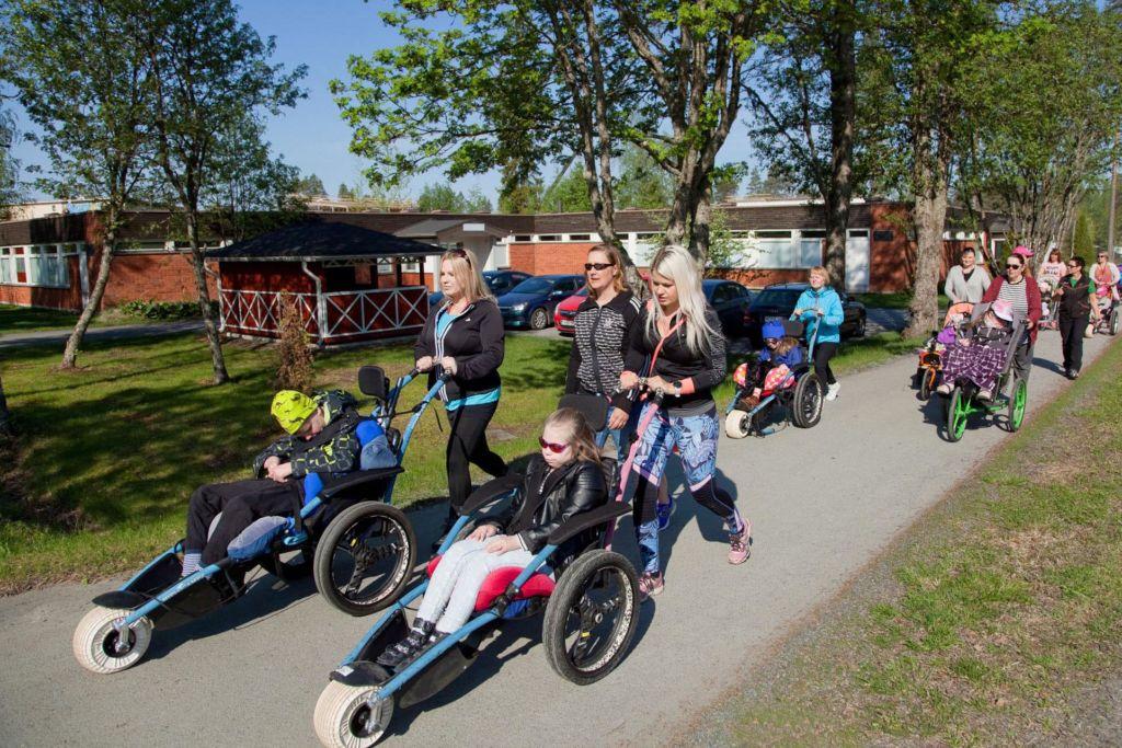 Kuvassa maastopyörätuoleja ja -kärryjä. Oppilaat istuvat kyydissä ja aikuiset työntävät niitä pitkin pyörätietä. Aurinko paistaa ja luonto vihertää, on kevät.