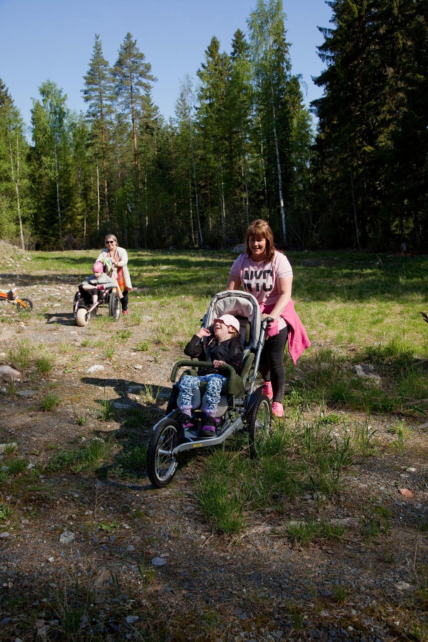 Kuvassa etualalla tyttö istuu Kimba-rattaissa ja nainen työntää niitä. Taempana Hippocampe maastopyörä, jonka kyydissä istuu tyttö ja nainen työntää niitä..