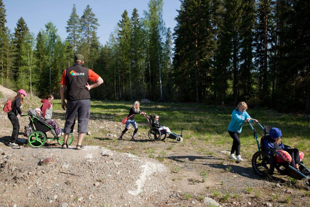 Kuvassa maastokärryt ja -rattaat mahdollistavat vaikeavammaisten lasten osallistumisen koulupäivän retkitoimintaan. Kolme lasten kanssa työskentelevää aikuista työntää maastokärryjä ja -rattaita ja lapset istuivat kyydissä. On kaunis aurinkoinen alkukesän päivä.