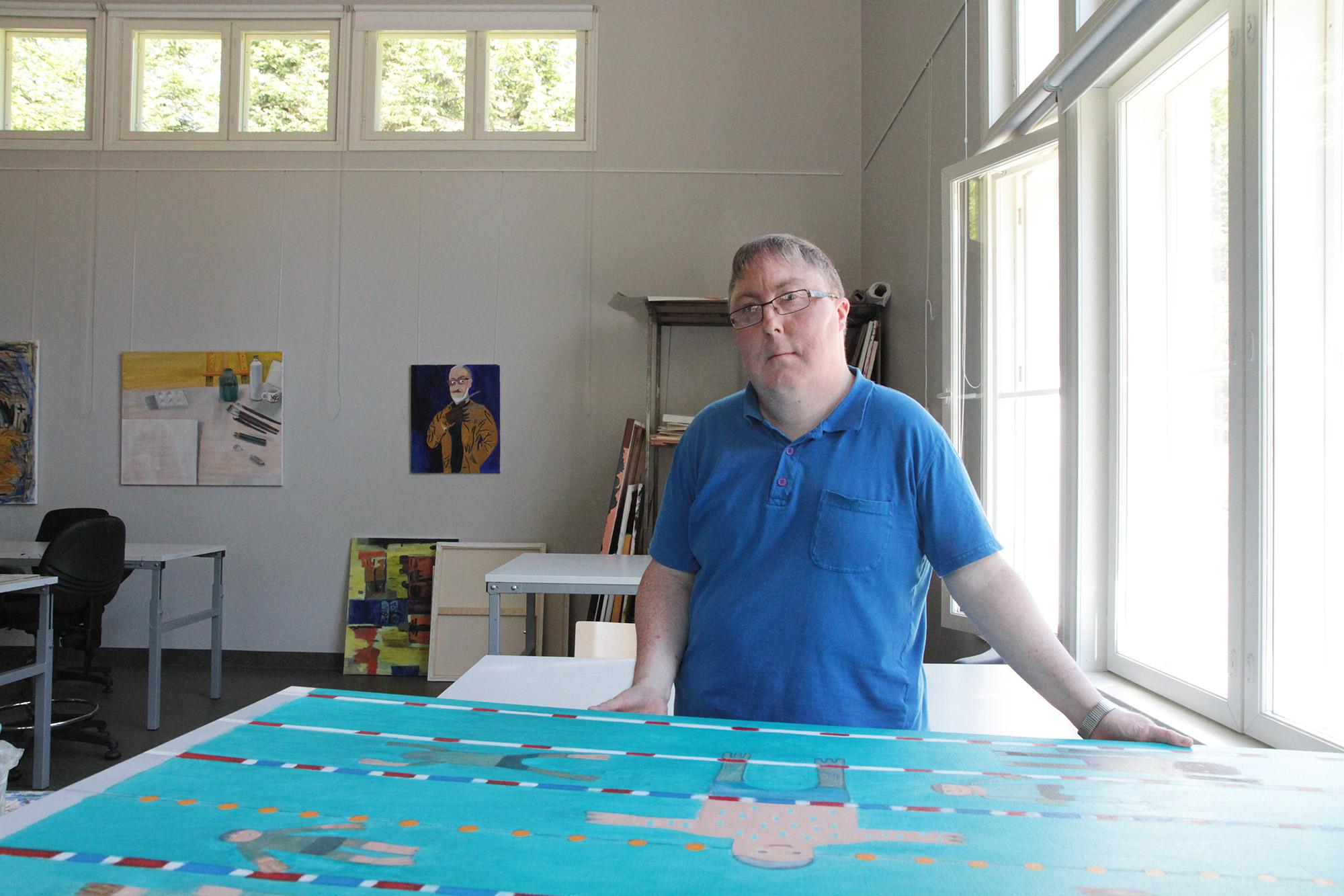 Mies seisoo pöydän takana. Pöydällä on suurikokoinen sininen maalaus.