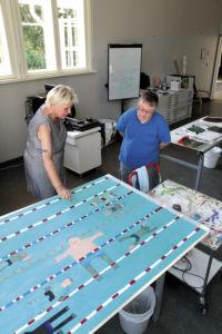 Nainen ja mies katsovat suurta sinistä maalausta, joka on pöydällä.