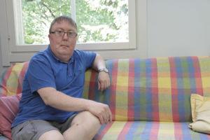 Mies istuu sohvalla ja katsoo kohti kameraa.