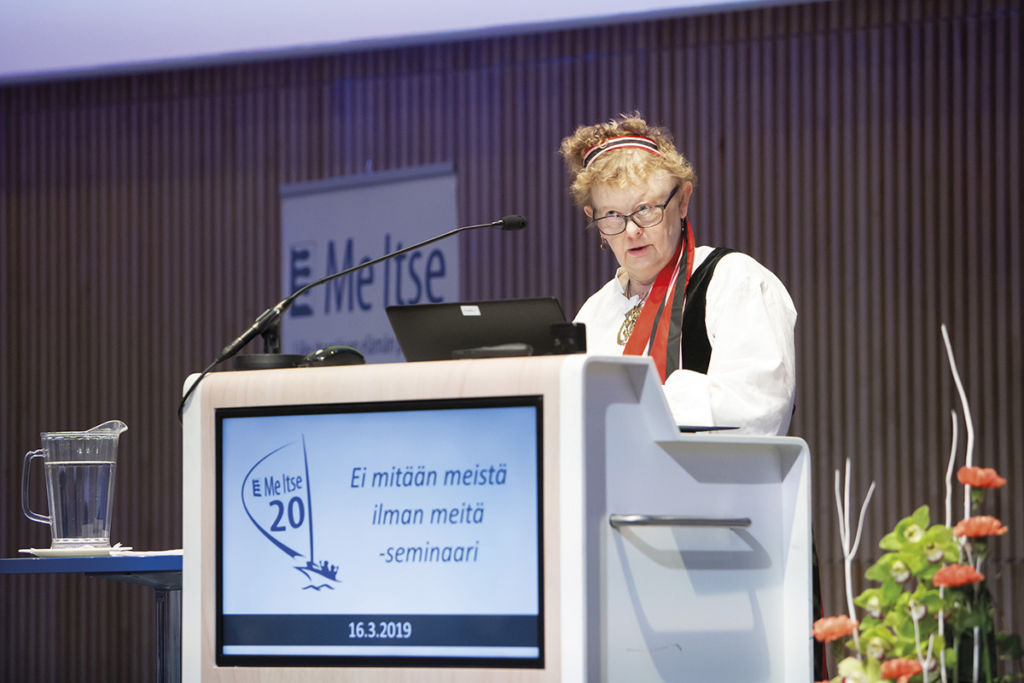 Ulla Topi on suuren yleisön edessä. Hän pitää puhetta ja katsoo yleisöä.
