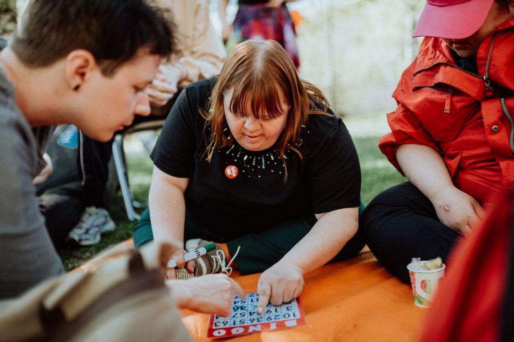 Ihmisiä istuu piknikviltillä ja pelaa yhdessä bingoa.