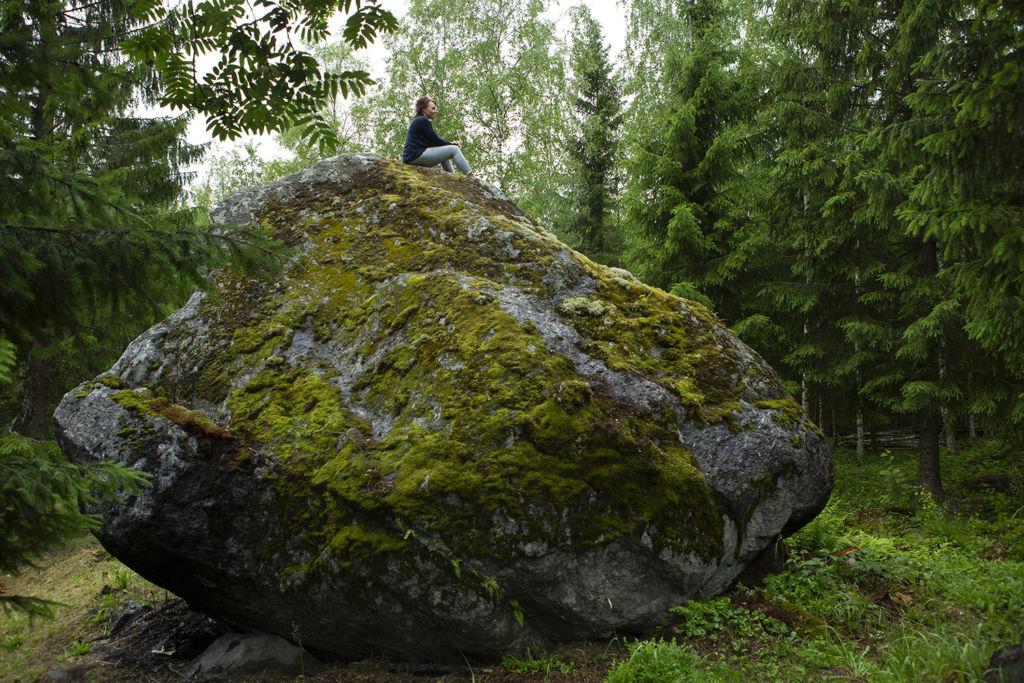Mari Tuhkanen istuu suuren kiven päällä