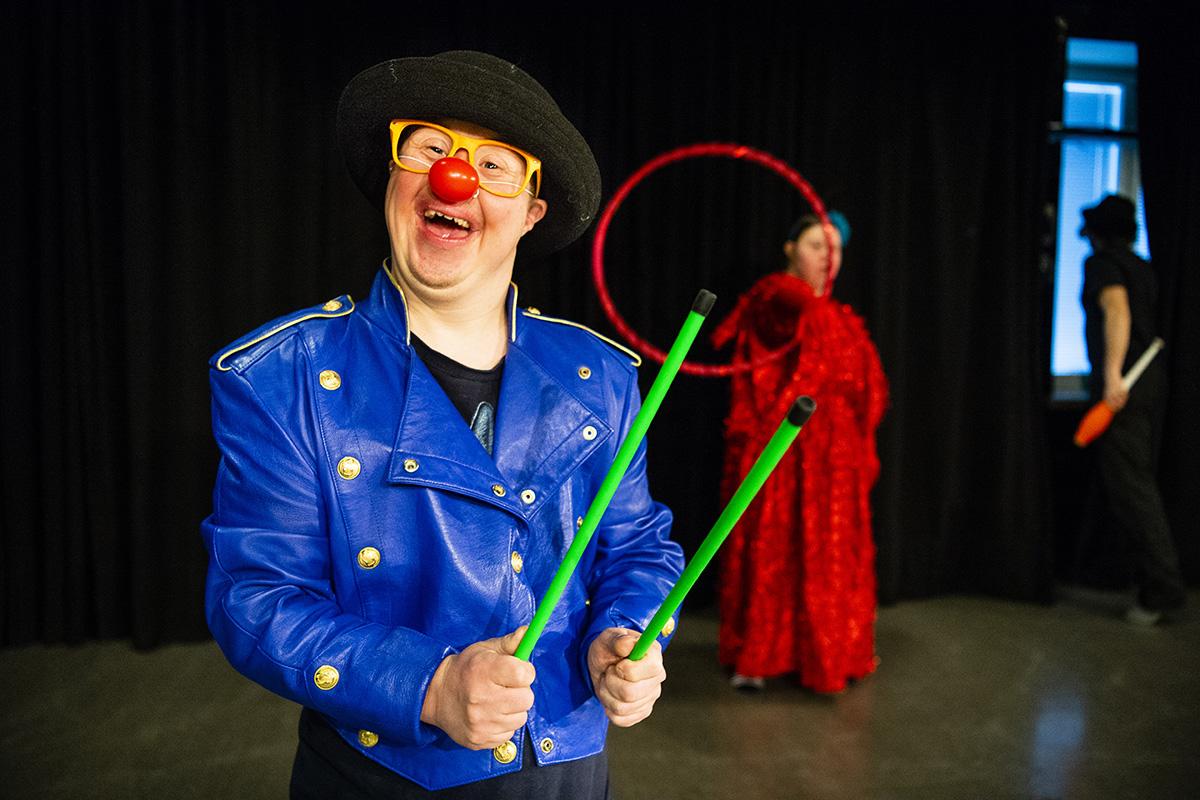 Hymyilevä sirkuspelle pitää kädessään rumpupalikoita.