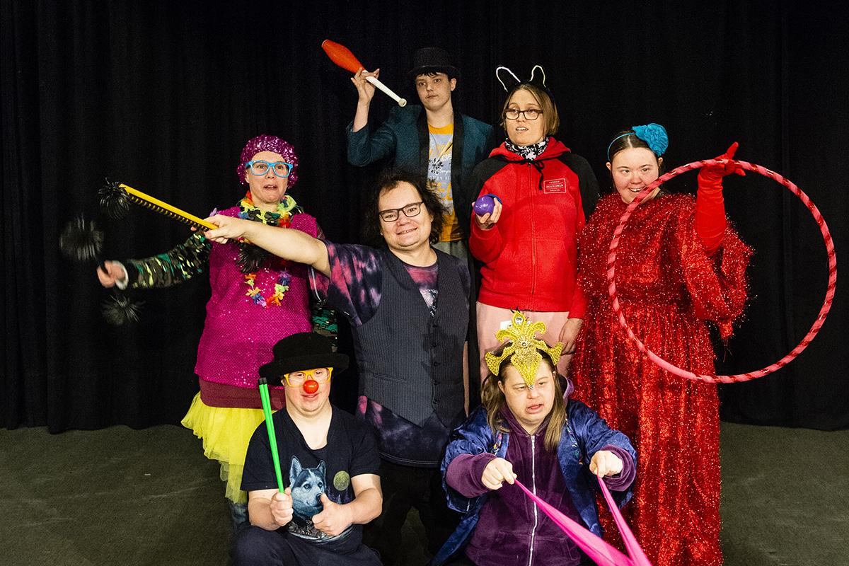 Värikkäästi pukeutunut sirkusryhmä poseeraa kuvaajalle.