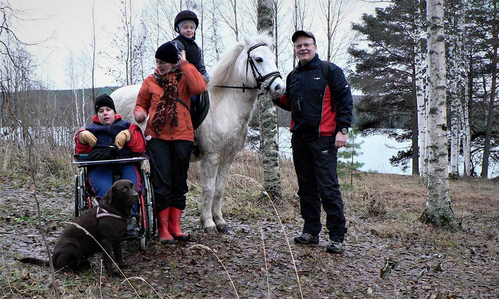 Perhe metsäretkellä ponin kanssa.