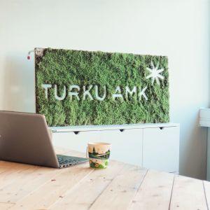 Pöydällä tietokone ja kahvikuppi