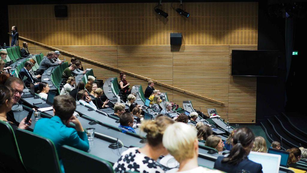 Auditoriossa istuvia ihmisiä