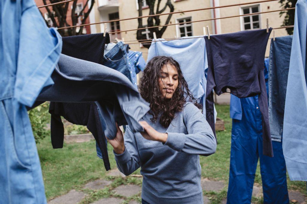 Nainen seisoo keskellä pyykinarua, jossa roikkuu sinisiä vaatteita.